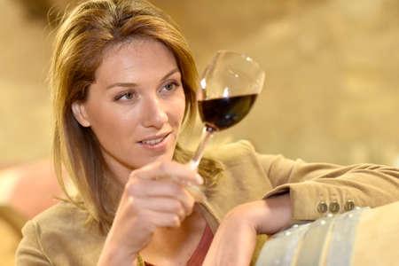 女性のセラーでワインの試飲