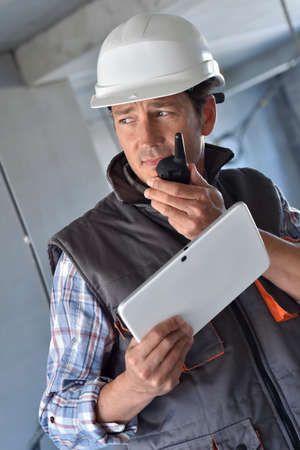 walkie: Entrepreneur on building site using walkie talkie