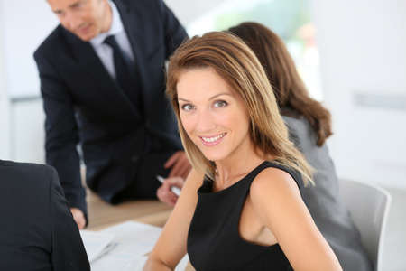 black dress: Smiling attractive businesswoman attending meeting Stock Photo