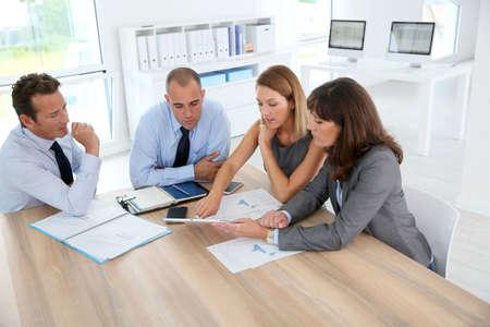 gerente: Grupo de hombres de negocios reunidos alrededor de la mesa de la tableta wih