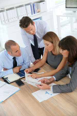 Group of business people meeting around table wih tablet photo