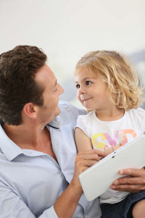 family sofa: Father and daughter playing with digital tablet Stock Photo