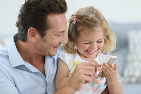 single parent: Man with 3-year-old girl playing with smartphone