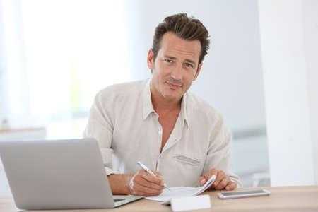 Lächelnde attraktive Mann arbeitet von zu Hause aus