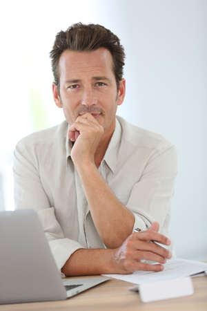 Smiling attractive man working from home Stock Photo
