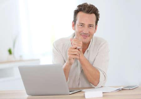 Lächelnde attraktive Mann arbeitet von zu Hause aus Standard-Bild