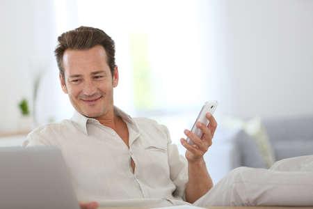 Ontspannen man werken vanuit huis en met behulp van smartphone