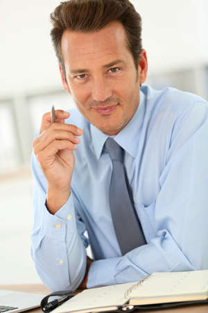 Businessman in office writing on agenda