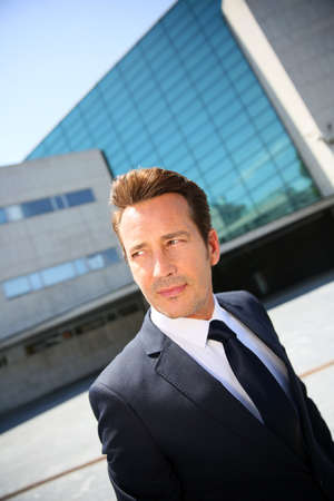 40s adult: Portrait of businessman standing in front of modern building