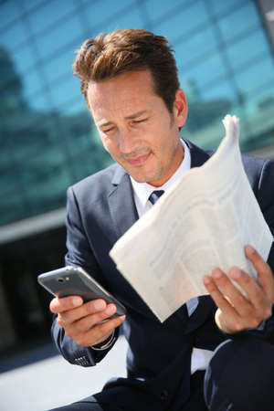 Businessman sitting outside office with smarphone and newspaper photo