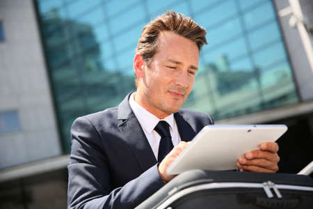 Businessman sitting outside office and using tablet photo