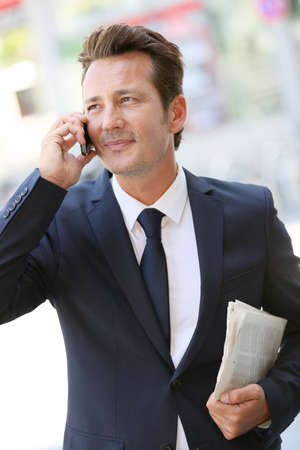 telephone salesman: Attractive businessman in town talking on mobile phone