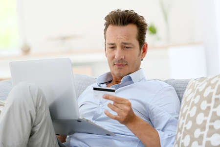 Man at home buying on internet Stock Photo