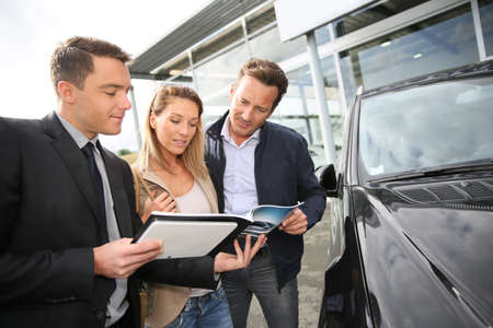 Car dealer showing vehicles to couple