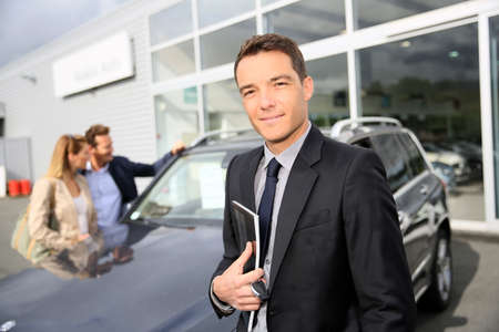 Smiling car dealer standing by vehicle, clients in background photo