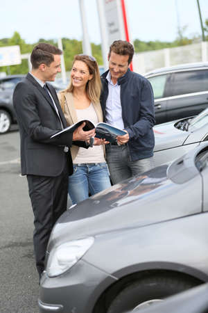 Car dealer showing vehicles to couple  photo