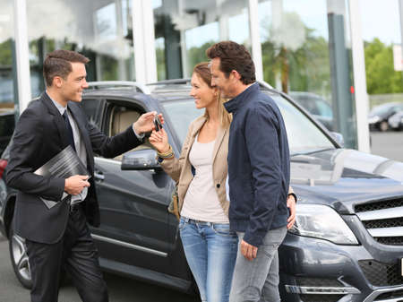 automobile dealers: Salesman in car dealership giving keys to clients Stock Photo