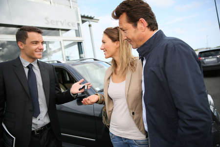 Salesman in car dealership giving keys to clients photo