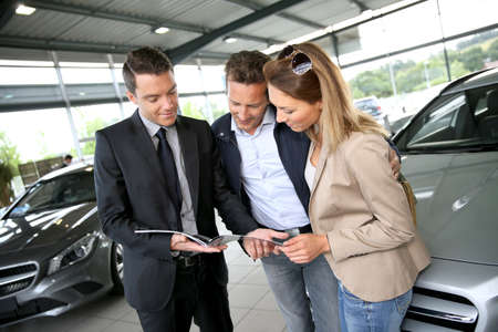 car dealers: Couple in car dealership looking at brochure with salesman Stock Photo