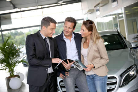 Couple in car dealership looking at brochure with salesman photo