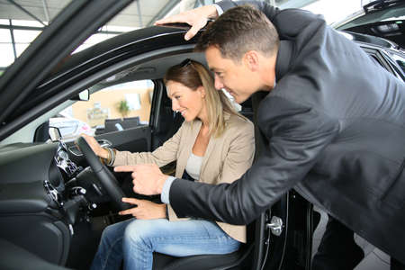 car shop: Car dealer showing vehicle to woman Stock Photo