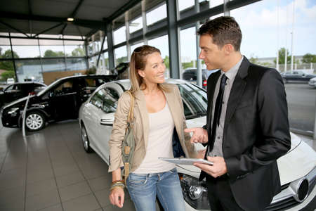 car dealers: Car dealer showing vehicle to woman Stock Photo