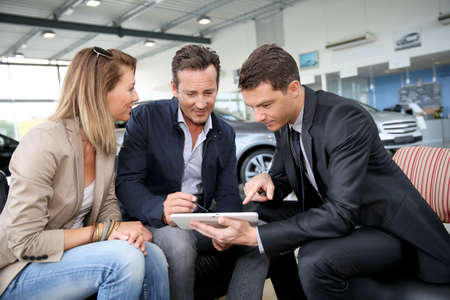 Couple signing car purchase order on digital tablet Фото со стока