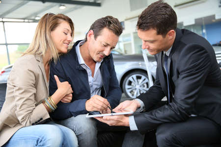 Couple signing car purchase order on digital tablet Stock Photo