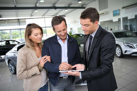 Couple signing car purchase order on digital tablet Stock Photo - 29377000