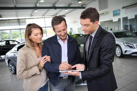 orden de compra: Pareja de firmar la orden de compra del coche en la tableta digital
