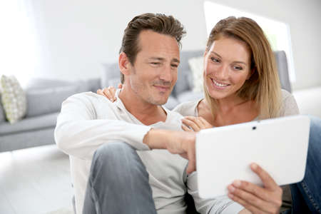 websurfing: Middle-aged couple websurfing with tablet at home