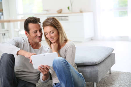 couple couch: Middle-aged couple websurfing with tablet at home