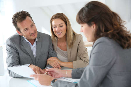 Couple meeting financial adviser for loan granting photo