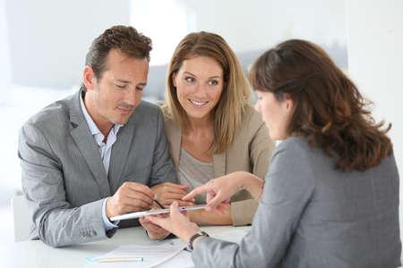 firmando: Pareja firmar concesión de préstamos en la tableta digital Foto de archivo