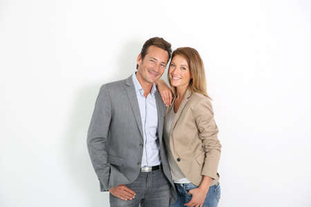 Smiling middle-aged couple standing on white background