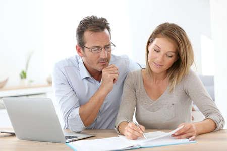 pareja en casa: Pareja en casa trabajando en la computadora portátil Foto de archivo