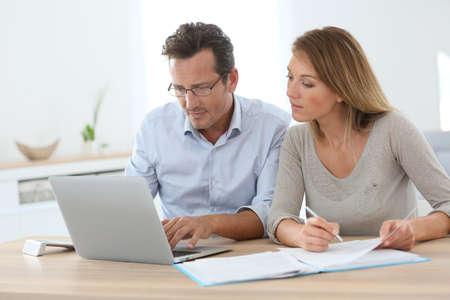 casal: Pares em casa trabalha no computador portátil