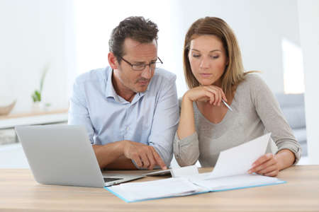 working at home: Pareja en casa trabajando en la computadora port�til Foto de archivo