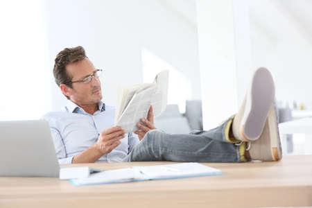 Man krant lezen met gestrekte benen op tafel