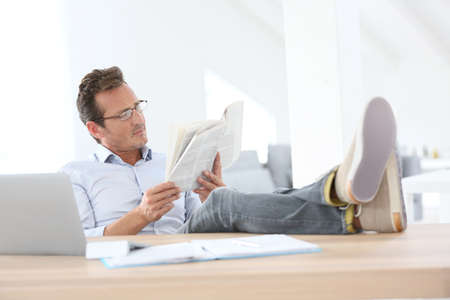 Man reading newspaper with stretched legs over table