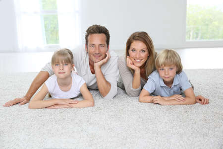 Happy family of four laying on carpet at home