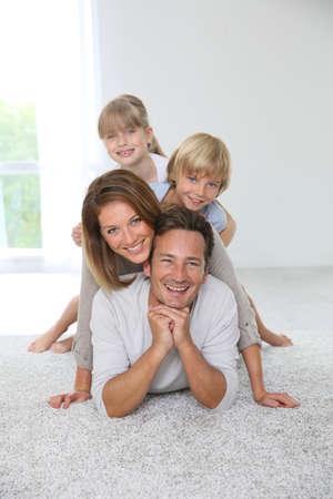 piramide humana: Familia feliz de cuatro tirado en la alfombra en su casa