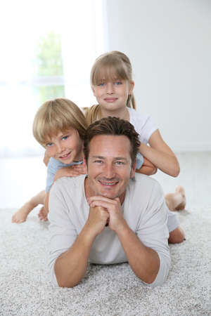 Daddy with kids laying on carpet photo