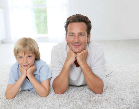 Father and son laying on carpet at home photo