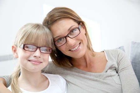 woman on couch: Portrait of smiling woman and girl wearing eyeglasses