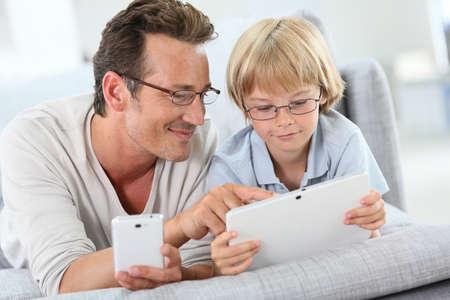 papa: P�re et fils jouant avec tablette et smartphone Banque d'images