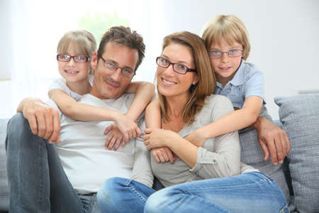 4 つの身に着けているメガネの幸せな家族の肖像画