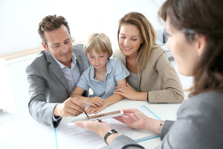 planificacion familiar: Firma Family contrato de compra de vivienda en la tableta Foto de archivo