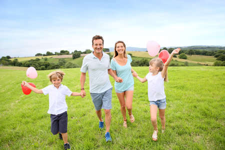 Family running in countryside, kids holding balloons photo