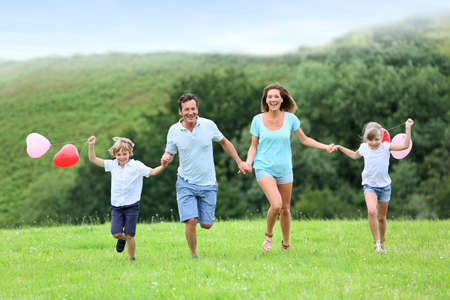 Family running in countryside, kids holding balloons Stock Photo